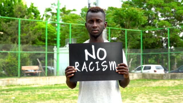 Young African Protestor is holding cardboard ''NO RACISM''