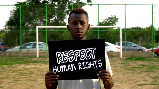 Young African Protestor is holding cardboard ''RESPECT HUMAN RIGHTS''