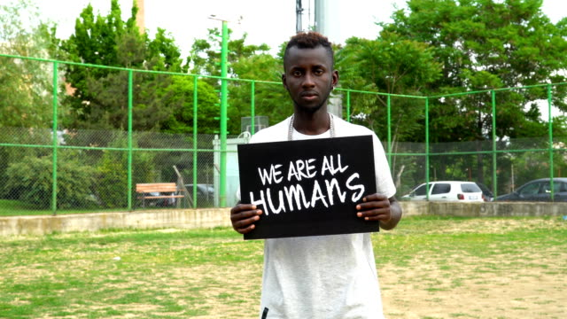 Young African Protestor is holding cardboard ''WE ARE ALL HUMANS''