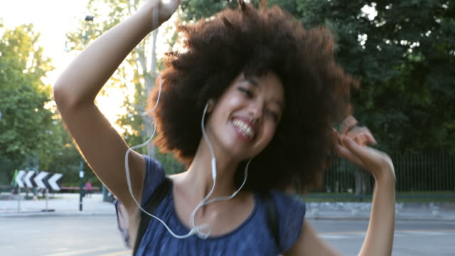 Young african teenager dancing in the city streets - video