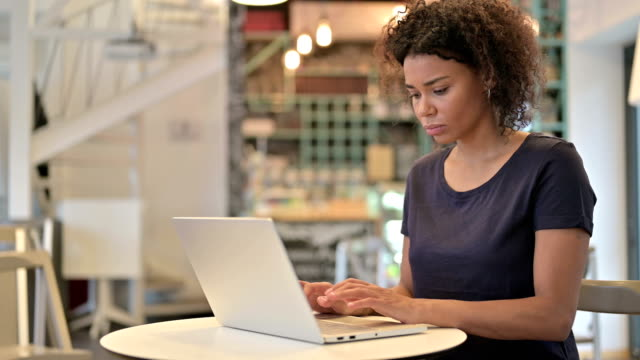 Young African Woman Reacting to Loss on Laptop in Cafe