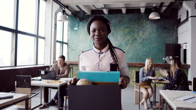 Young african woman recently hired for corporate job comes into new office. Female holds box with personal belongings video