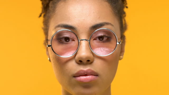 Young african woman taking off eyeglasses looking shocked on camera, dermatology