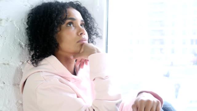 junge afrikanische frau denken und brainstorming, sitzt am fenster - introspektion stock-videos und b-roll-filmmaterial