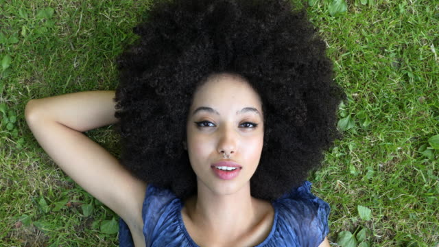 Young african woman with arms open enjoying fresh air in summertime - video
