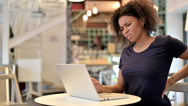 Young African Woman with Back Pain using Laptop in Cafe - vídeo