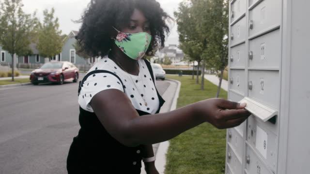 unga afroamerikanska par i tjugoårsåldern walking till en brevlåda till post i sin omröstning för att rösta - skicka aktivitet bildbanksvideor och videomaterial från bakom kulisserna