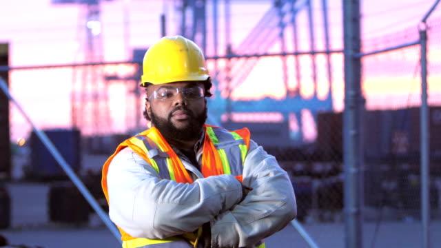 afroamerikanischen jungen mann, der arbeitet im verschiffungshafen - bauarbeiterhelm stock-videos und b-roll-filmmaterial