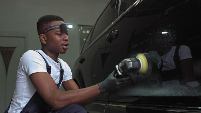 en ung afroamerikan polerar en bil. bil detaljer - män använder maskiner bil polermaskiner underhåll för att ta bort märken reparation enligt ytan av bilens färg innan du fortsätter att belägga keramik - wheel black background bildbanksvideor och videomaterial från bakom kulisserna