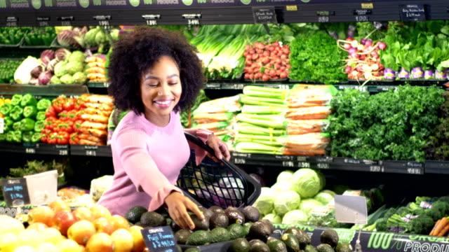 junge afroamerikanerin kauft lebensmittel - fülle stock-videos und b-roll-filmmaterial