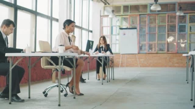 若いアフリカ系アメリカ人の女性のハイヒールマネージャーは、彼女の机に椅子に乗って楽しんでいます。男性の同僚が彼女を助ける。ロフトスタイルでコワーキング。オフィスライフ。ク� ビデオ