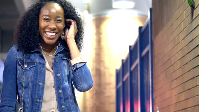 vídeos de stock e filmes b-roll de young african-american woman in city walks up to camera - afro americano