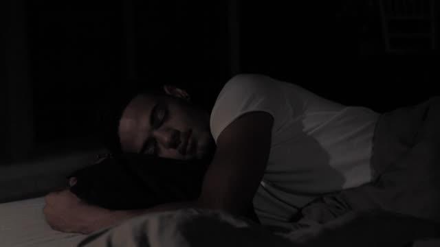 giovane afro-americano che dorme con il cuscino e si muove di notte nel suo letto in camera da letto. insonnia, infastidito, stressato, stanco. - sonnecchiare video stock e b–roll