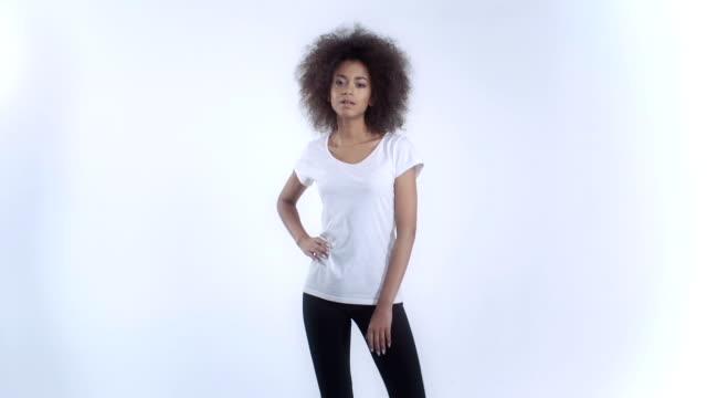 Joven mujer afro americano en una camiseta blanca posando sobre fondo blanco. - vídeo