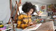 istock Young afro woman drawing 1163909918