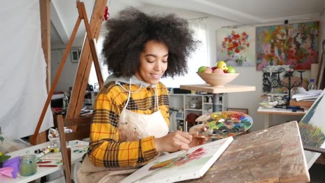 stockvideo's en b-roll-footage met jonge afro vrouw tekening - afro amerikaanse etniciteit
