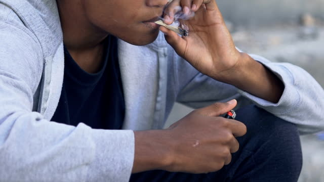 vídeos de stock, filmes e b-roll de jovens afro-americanos viciados em fumar masculino ao ar livre, maus hábitos e drogas - erva