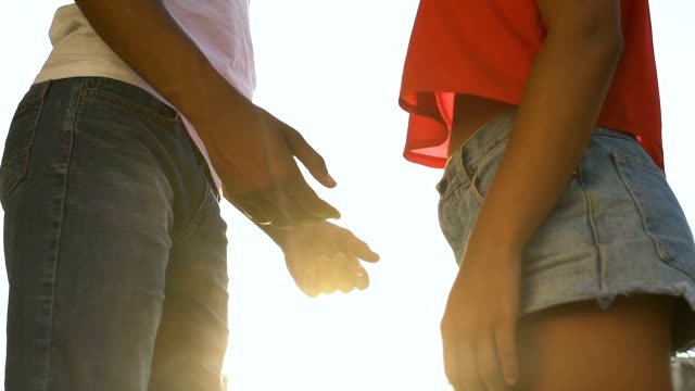 Video Young Afro-American couple putting hands together outdoors, love, bottom view