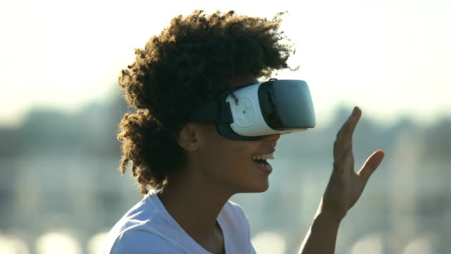 young afro-american lady wearing virtual reality digital glasses device outdoors - навык стоковые видео и кадры b-roll