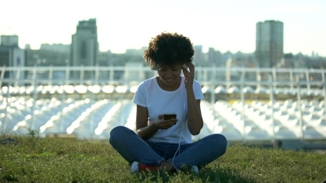 Young afro-american woman listening to music in headset, sitting on lawn, relax