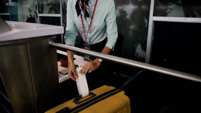 Young airline attendant attaching label on traveler's suitcase
