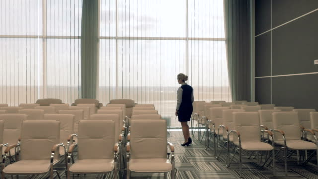 Young airport employee in the conference hall checks the room video