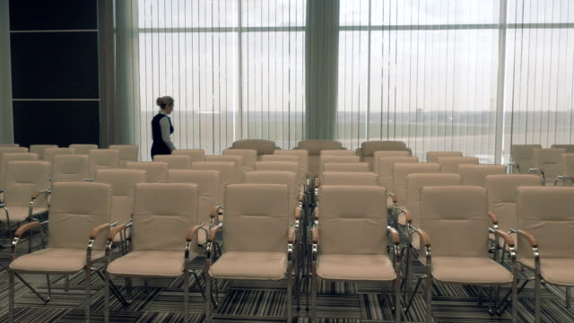 Young airport worker in the conference hall checks the room video