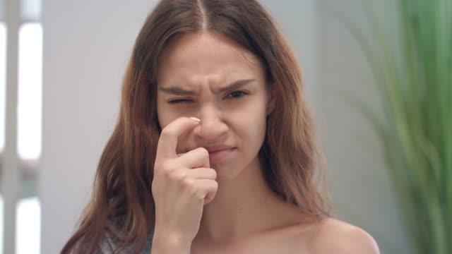 genç alerjik kadın burun ön kamera çizilmeye. kadın grip belirtileri hissi - burun vücut parçaları stok videoları ve detay görüntü çekimi