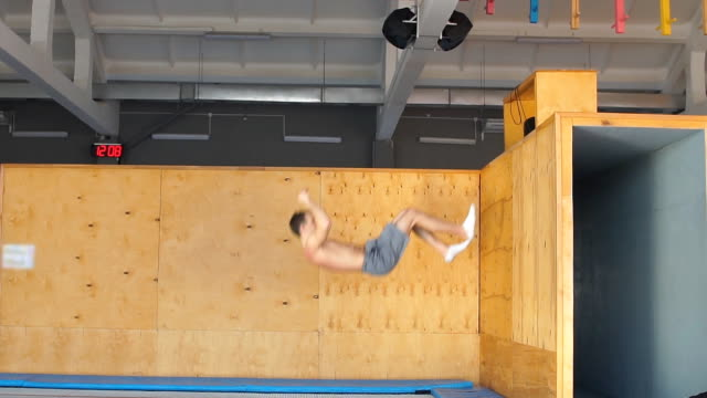 young ambitious athlete is doing exercise on the air after pushing off the wooden board - acrobazia video stock e b–roll