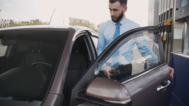 Young american businessman getting into black car at gas station in summer Young american businessman getting into black car at gas station in summer. Handsome bearded guy wants to drive after refueling auto at gasoline service on city street. Caucasian man wearing shirt and tie. button down shirt stock videos & royalty-free footage