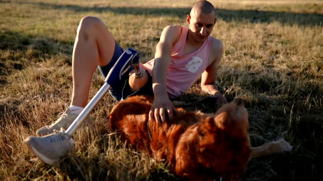 Young amputee enjoying the time in the park with his dog Young amputee with a artificial leg, enjoying his time with his dog, a golden retriever. artificial limb stock videos & royalty-free footage