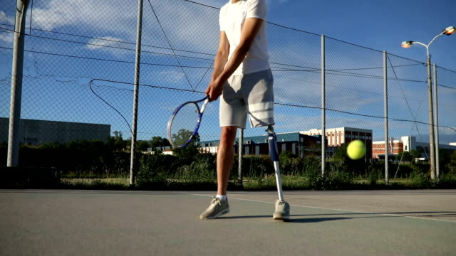 Young amputee playing tennis Young amputee with a artificial leg, enjoying his time outdoors by playing tennis on a tennis court. artificial limb stock videos & royalty-free footage