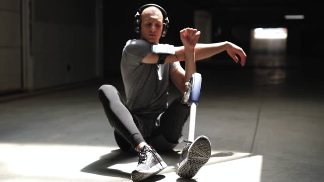 Young Amputee Sportsman Stretching Before Training Pretty Young Amputee Sportsman Stretching His arms Sitting On Pavement Before Training artificial limb stock videos & royalty-free footage