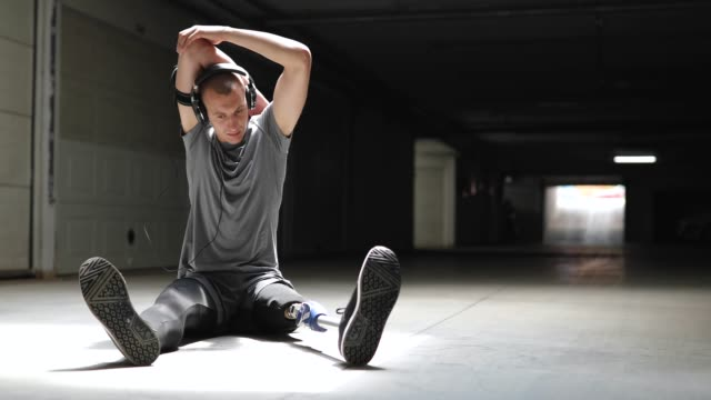 Young Amputee Sportsman Stretching Before Training Pretty Young Amputee Sportsman Stretching His arms Sitting On Pavement Before Training amputee stock videos & royalty-free footage