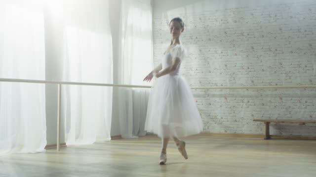 Young and Beautiful Ballerina Dances Energetically but Gracefully on Her Pointe Ballet Shoes, She's Spinning. She's Wearing White Tutu Dress. Studio is Sunny and Modern. video