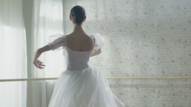 Young and Beautiful Ballerina Gracefully Dances on Her Pointe Ballet Shoes. She's Wearing White Tutu Dress. Studio is Sunny and Modern. In Slow Motion. Young and Beautiful Ballerina Gracefully Dances on Her Pointe Ballet Shoes. She's Wearing White Tutu Dress. Studio is Sunny and Modern. In Slow Motion. Shot on RED EPIC-W 8K Helium Cinema Camera. tulle netting stock videos & royalty-free footage