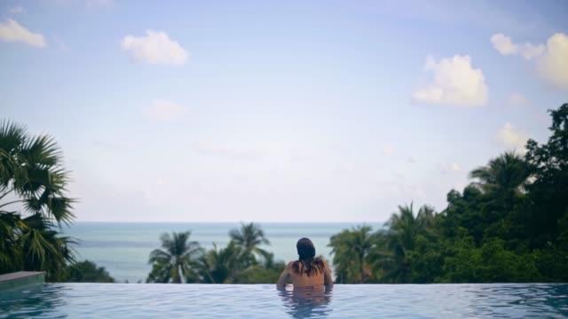 熱帯の島のオープンスカイの下のプールで若くて美しい女の子が海を見て. - 異国情緒点の映像素材/bロール