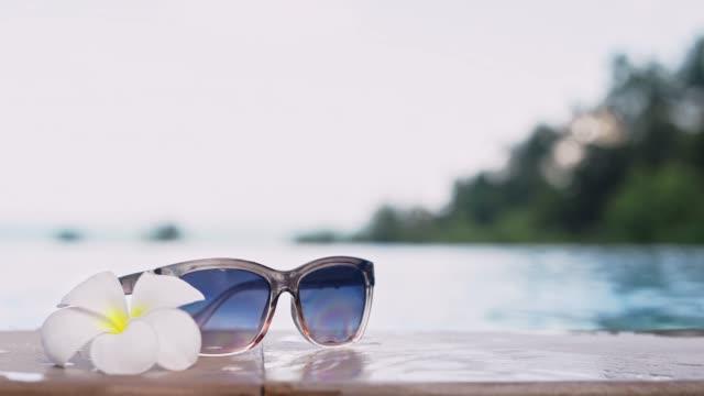 vídeos de stock e filmes b-roll de young and beautiful girl wears sunglasses in a pool on a tropical island. - mulher natureza flores e piscina