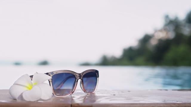 vídeos de stock e filmes b-roll de young and beautiful girl wears sunglasses in a pool on a tropical island - mulher natureza flores e piscina