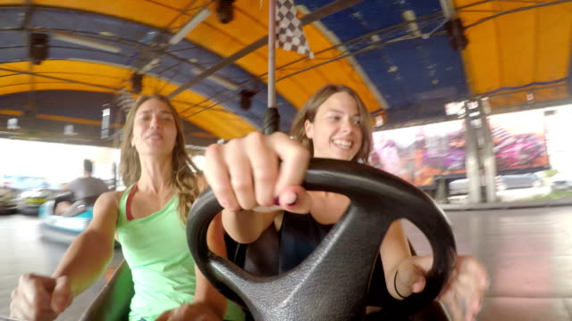 Young and beautiful girls friends riding a electric car in amusement park