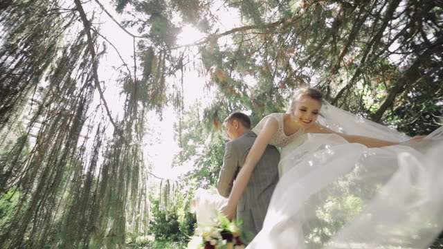 Young and beautiful wedding couple together in the park. Lovely groom and bride. Wedding day. Slow motion
