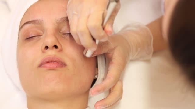 vídeos de stock e filmes b-roll de a young and beautiful woman is given a diamond facial cleansing. - tratamento em spa