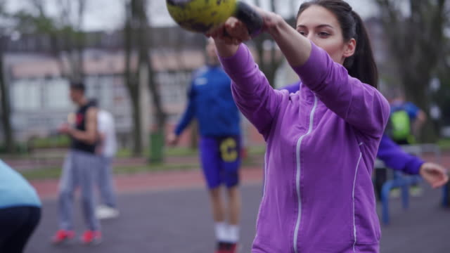 Young and beautiful woman train with kettlebell outdoors