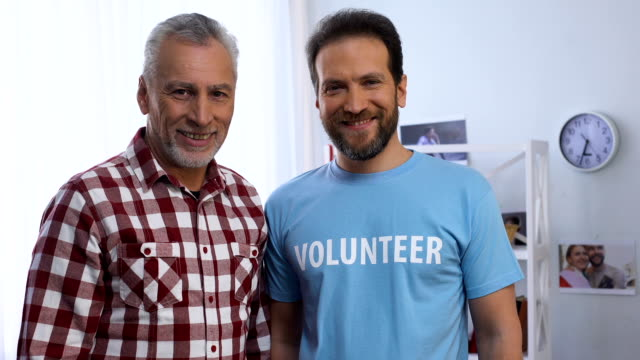 young and elderly men showing volunteer word on t-shirt to camera, charity - maglietta video stock e b–roll