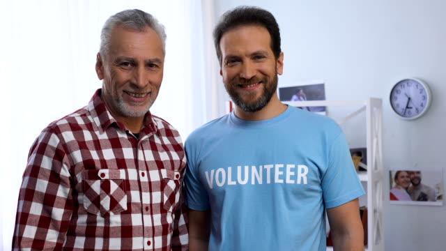 stockvideo's en b-roll-footage met jonge en oudere mannen tonen vrijwilliger woord op t-shirt aan de camera, liefdadigheid - t shirt