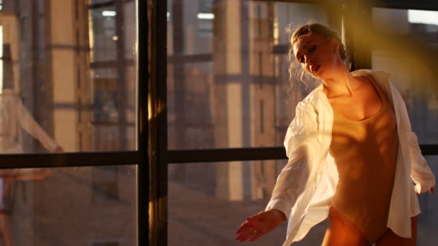 A young and energetic girl dancing contemp. In a loft studio with large panoramic windows, a woman in a body and shirt is dancing A young and energetic girl dancing contemp. In a loft studio with large panoramic windows, a woman in a body and shirt is dancing dance studio stock videos & royalty-free footage