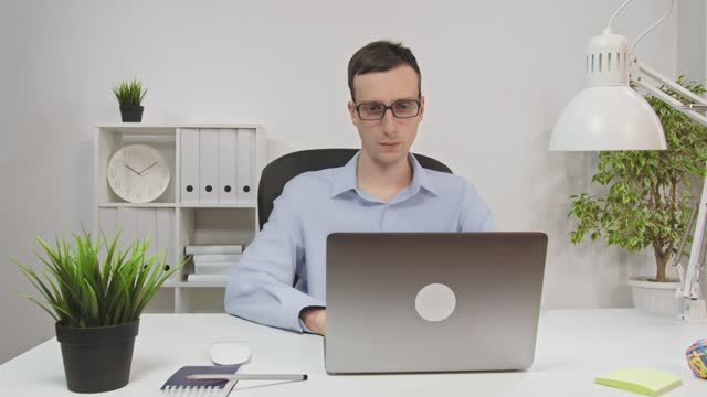 Young and handsome office worker sitting at his desk works on a laptop. In the background modern office