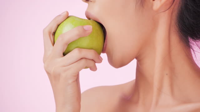 Young and happy woman eating apple on pink background. Clean and balanced healthy food concept.Healthy food,diet and fitness concept.Organic food.Health care and medicine concept.Video: Diverse Portraits - vídeo