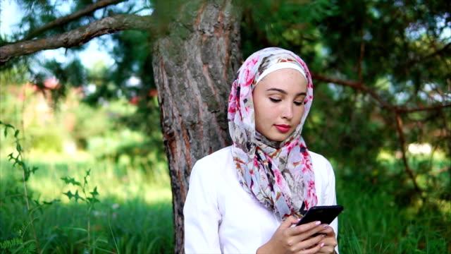 unga och moderna muslimska kvinnan talar kommunicerar via mobiltelefon med vänner - anständig klädsel bildbanksvideor och videomaterial från bakom kulisserna