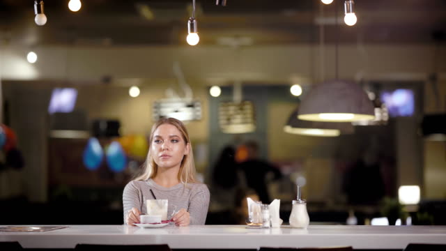 A young and pretty woman finished her coffee latte in a restaurant, the lady is waiting for an invoice for her lunch and wants to pay video